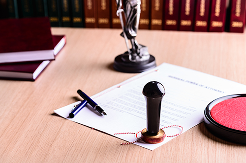 Stamp of the notary on signed power of attorney. Pen and Themis with scales of justice in the background.